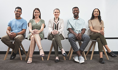 Buy stock photo Portrait of a group of businesspeople sitting together in a line against a white wall