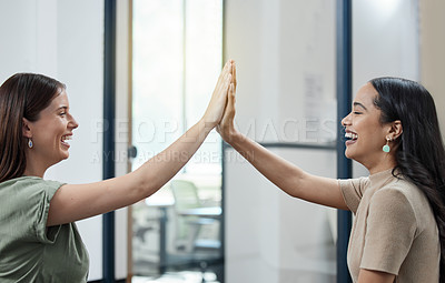 Buy stock photo Shot of two businesswomen giving each other a high five in an office