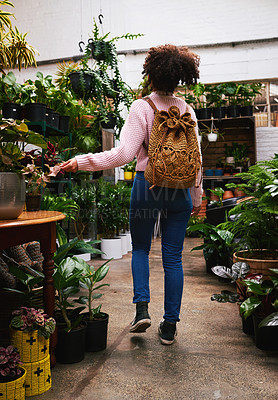 Buy stock photo Shot of a young woman shopping for plants in a nursery