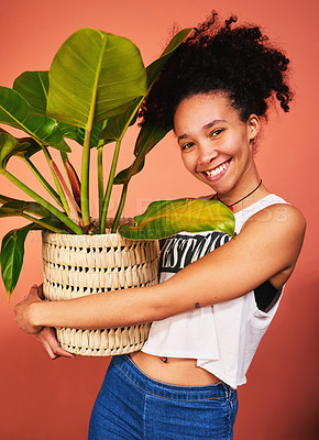 Buy stock photo Shot of a woman holding a pot plant against a studio background