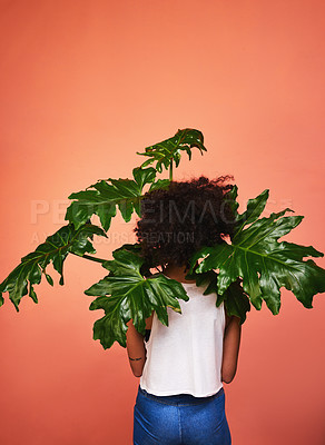 Buy stock photo Shot of the back of a woman holding a plant against a studio background