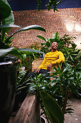Buy stock photo Shot of a young man sitting in a plant nursery