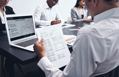 Buy stock photo Shot of a businessman checking paperwork at his desk in his office