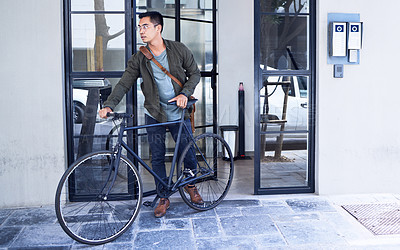 Buy stock photo Shot of a young man using a bicycle in the city