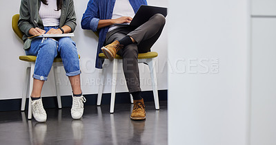 Buy stock photo Shot of two unrecognizable people using their devices while waiting to be interviewed in a modern office