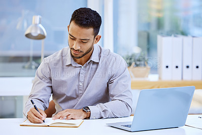 Buy stock photo Shot of a businessman making notes while sitting at his desk