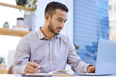 Buy stock photo Shot of a businessman making notes while working on his laptop at his desk