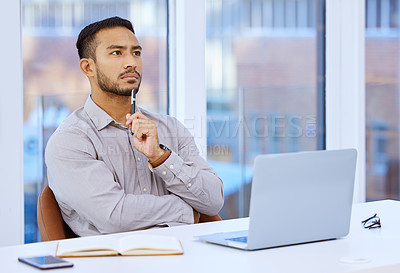 Buy stock photo Shot of a young businessman looking thoughtful while sitting at his desk