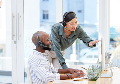 Buy stock photo Shot of a young businesswoman helping her male work colleague