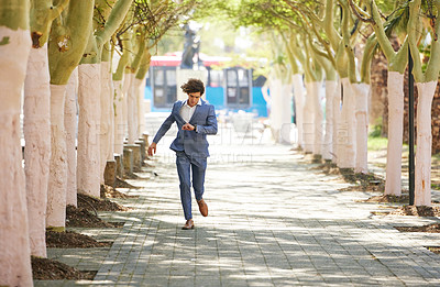 Buy stock photo Full body shot of a young businessman  rushing down the street and checking his watch against an urban background