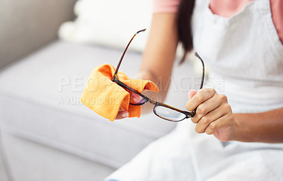 Buy stock photo Cropped shot of a woman cleaning her glasses while sitting at home