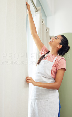 Buy stock photo Shot of a young woman hanging clean curtains at home