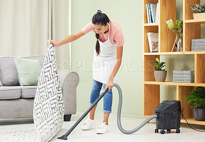 Buy stock photo Shot of a young woman vacuuming the living room