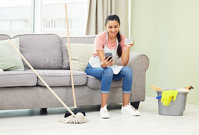 Buy stock photo Shot of a woman using her cellphone and drinking coffee while taking a break from cleaning at home