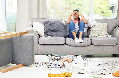 Buy stock photo Shot of a young woman feeling overwhelmed while sitting in a messy living room