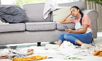 Buy stock photo Shot of a woman sitting on the floor with her cellphone in a messy living room