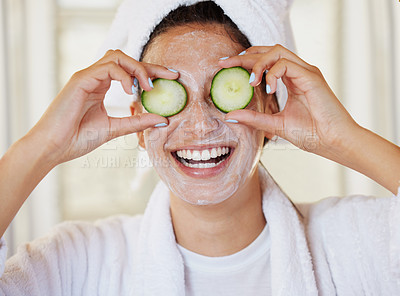 Buy stock photo Shot of a beautiful young woman holding cucumbers in front of her eye during her beauty routine