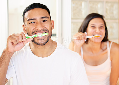 Buy stock photo Shot of a happy young couple brushing their teeth in the bathroom at home
