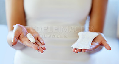 Buy stock photo Cropped shot of an unrecognizable woman holding a tampon and a pad in her hands