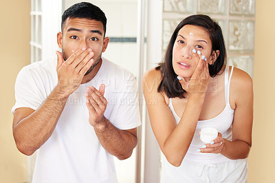 Buy stock photo Shot of a young couple moisturising their skin at home