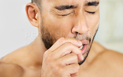 Buy stock photo Cropped shot of a young man using tweezers to pluck his nose hair