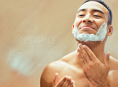 Buy stock photo Shot of a handsome young man applying shaving cream to his face