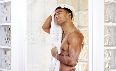 Buy stock photo Shot of a man drying himself after taking a shower