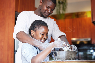 Buy stock photo Shot of a father teaching his daughter how to bake in the kitchen at home