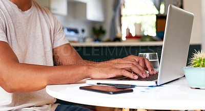Buy stock photo Cropped shot of an unrecognizable man sitting alone and using his laptop to work from home