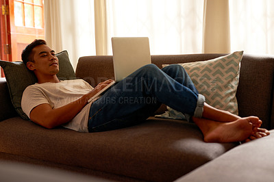 Buy stock photo Shot of a handsome young man lying down on his sofa in his living room and using his laptop for work