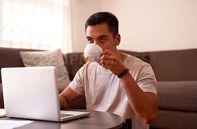 Buy stock photo Shot of a handsome young man sitting in his living room and drinking tea while working from home
