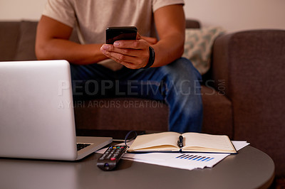 Buy stock photo Cropped shot of an unrecognizable man sitting alone in his living room and using his laptop and cellphone to work