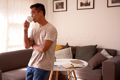 Buy stock photo Shot of a handsome young man standing alone in his living room and looking contemplative while drinking tea