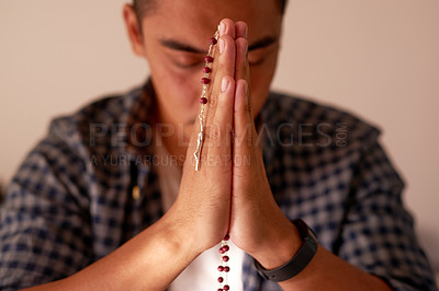 Buy stock photo Shot of a handsome young man sitting alone at home and using his rosary during prayer