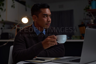 Buy stock photo Shot of a young businessman taking a coffee break while working late at home