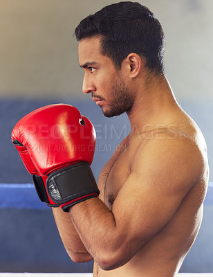 Buy stock photo Cropped shot of a handsome young male boxer standing with his guard up during a fight in the ring