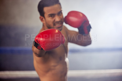 Buy stock photo Cropped portrait of a handsome young male boxer striking towards the camera during a fight in the ring