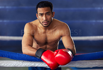 Buy stock photo Cropped portrait of a handsome young male boxer leaning against the ropes after a fight in the ring