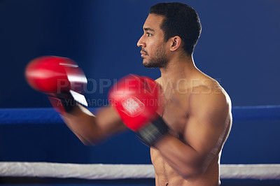 Buy stock photo Cropped shot of a handsome young male boxer striking swiftly during a fight in the ring