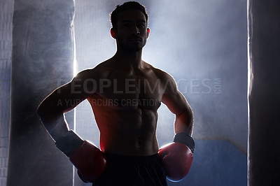 Buy stock photo Cropped portrait of a silhouetted young male boxer standing with his hands on his hips after a workout on the punching