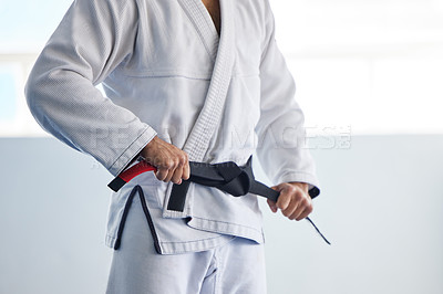 Buy stock photo Cropped shot of an unrecognizable male martial artist tying his belt in the gym