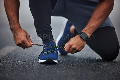 Buy stock photo Closeup shot of an unrecognisable man tying his shoelaces while exercising outdoors