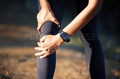 Buy stock photo Closeup shot of an unrecognisable woman holding her knee in pain while exercising outdoors