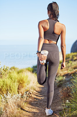 Buy stock photo Rearview shot of a sporty young woman stretching her legs while exercising outdoors
