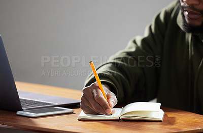 Buy stock photo Shot of an unrecognizable man writing in a notebook in an office