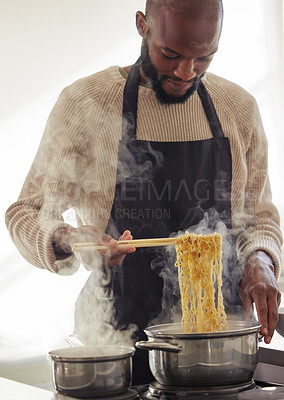 Buy stock photo Cropped shot of a handsome young man cooking on his stove in the kitchen at home
