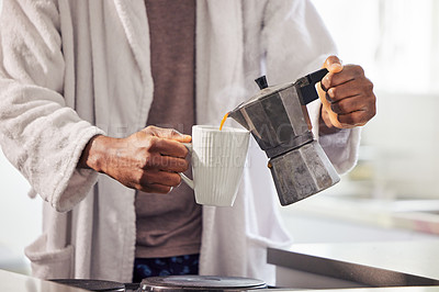 Buy stock photo Shot of an unrecognizable man pouring coffee into a cup at home