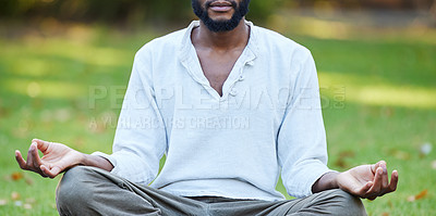 Buy stock photo Cropped shot of an unrecognizable young man meditating while practicing yoga outside at the park
