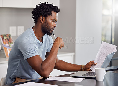 Buy stock photo Shot of a man going through some paperwork and looking worried at home