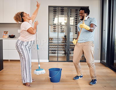 Buy stock photo Shot of a young couple singing and dancing while cleaning at home